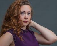 La belleza adolescente en vestido púrpura con el codo señaló a la derecha Imagen de archivo