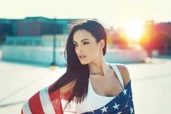 La belleza americana cubierta por la estrella spangled la bandera en puesta del sol Fotos de archivo libres de regalías