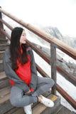 La belleza china lleva el abrigo esquimal de la montaña se sienta en las escaleras en la montaña de la nieve foto de archivo