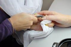La belleza clava el amo de la manicura en el trabajo. Foto de archivo libre de regalías