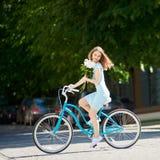 La belleza joven en la bicicleta del vintage fijó sus peonías, día soleado Imagenes de archivo
