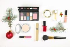 La bellezza compone l'insieme del cosmetico con la decorazione di natale e presenta in mani che del ` s della donna il piano mett Immagini Stock