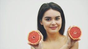 La bellezza di una donna proviene dal pompelmo arancio dell'agrume con pelle sana del corpo Vitamina fresca attraente studio stock footage