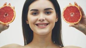 La bellezza di una donna proviene dal pompelmo arancio dell'agrume con pelle sana del corpo Vitamina fresca attraente studio archivi video