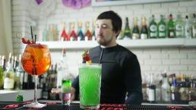 La bevanda alcolica con le fragole fresche sta sullo scrittorio della barra e su fondo unfocused del barista esegue l'acrobazia video d archivio