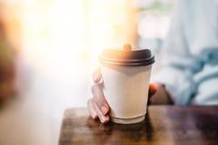 La bevanda calda in tazza di carta in mani si chiude su Immagine Stock