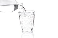 La bevanda gassosa trasparente ha versato in un contenitore trasparente Immagini Stock Libere da Diritti