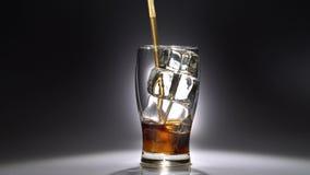 La bevanda in un vetro con ghiaccio è bevuta attraverso un tubo Luce da dietro video d archivio