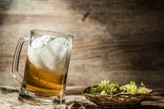 La bière écumeuse a versé dans la tasse Images libres de droits