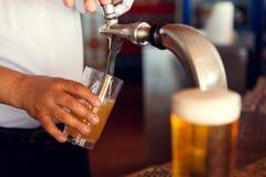 La bière pression versent dedans un verre Images libres de droits