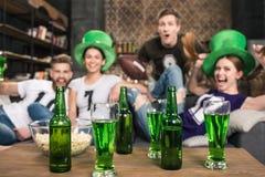 La bière verte dans des bouteilles et les verres s'approchent des amis Images stock
