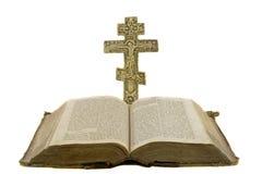 La bibbia aperta dell'annata molto vecchia e la grande chiesa attraversano Fotografia Stock