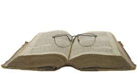 La bibbia aperta ed i vetri su esso hanno isolato sopra il whi Fotografia Stock