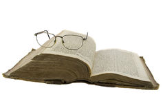La bibbia aperta ed i vetri su esso hanno isolato sopra il whi Immagini Stock