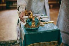 La bibbia della chiesa dell'altare esamina in controluce l'icona trasversale della corona Fotografia Stock Libera da Diritti