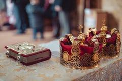 La bibbia della chiesa dell'altare esamina in controluce l'icona trasversale della corona Immagini Stock Libere da Diritti