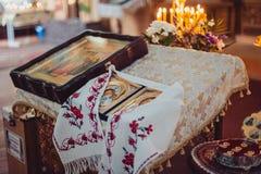 La bibbia della chiesa dell'altare esamina in controluce l'icona trasversale della corona Immagine Stock