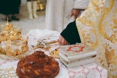 La bibbia della chiesa dell'altare esamina in controluce l'icona trasversale della corona Immagini Stock