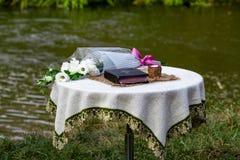 La bibbia, una candela e un mazzo dei fiori sono sui agains della tavola fotografia stock libera da diritti