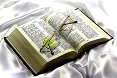 La bible et les verres sur un fond en soie blanc Photos stock