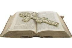 La bible ouverte de cru très vieux et la grande église croisent Images libres de droits