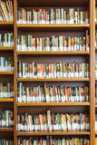 La biblioteca con gli scaffali di libro in pieno del libro ha sistemato nell'ordine sul rega Fotografia Stock