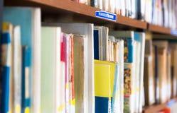 La biblioteca con gli scaffali di libro in pieno del libro ha sistemato nell'ordine sul rega Immagine Stock