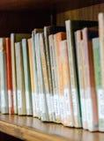 La biblioteca con gli scaffali di libro in pieno del libro ha sistemato nell'ordine sul rega Fotografie Stock Libere da Diritti