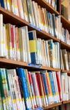 La biblioteca con gli scaffali di libro in pieno del libro ha sistemato nell'ordine sul rega Fotografia Stock Libera da Diritti