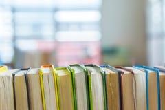 La biblioteca coperta dura prenota sullo scaffale con fondo vago Fotografia Stock