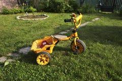 La bici amarilla de los niños en la hierba Fotos de archivo libres de regalías