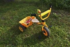 La bici amarilla de los niños en la hierba Fotos de archivo