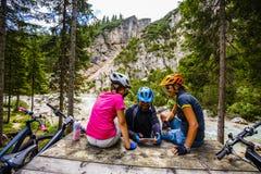 La bici de la familia monta en las montañas mientras que se relaja en el banco c Imagenes de archivo