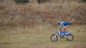 La bici de la muchacha muestra acrobático en competir con cruzado del moto del MX - jinete en una motocicleta de la suciedad Foto de archivo