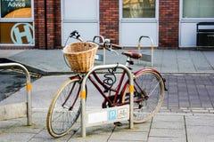 La bici de las señoras se parquea en un aparcamiento especial de la bicicleta en una pequeña ciudad inglesa imagenes de archivo