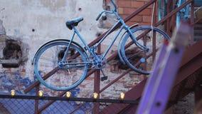 La bici del vintage cubierta por la pintura azul se cuelga en la pared de ladrillo próxima de la toma marrón almacen de metraje de vídeo