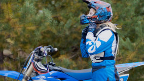 La bici della ragazza indossa un casco - corsa trasversale di moto del MX - cavaliere su un motociclo della sporcizia fotografia stock libera da diritti