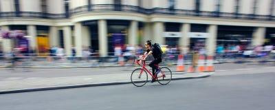 La bici di guida del ciclista digiuna attraverso la città Sfuocatura di velocità Fotografie Stock