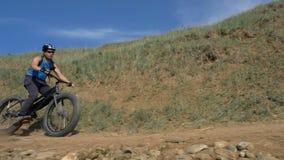 La bici grassa inoltre ha chiamato la bici della grasso-gomma o del fatbike di estate che guida sulla strada video d archivio