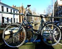 La bici o la bicicleta parqueó en un puente en Amsterdam, los Países Bajos Fotos de archivo