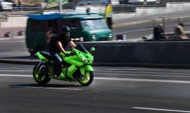 La bici verde Ninja del deporte de Yamaha viaja en la velocidad a través de la ciudad foto de archivo libre de regalías