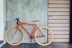 La bicicleta anaranjada parqueada adorna estilo moderno de la sala de estar interior Foto de archivo libre de regalías