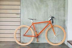 La bicicleta anaranjada parqueada adorna estilo moderno de la sala de estar interior Fotos de archivo libres de regalías