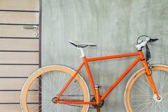 La bicicleta anaranjada parqueada adorna estilo moderno de la sala de estar interior Imagenes de archivo