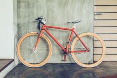 La bicicleta anaranjada parqueada adorna estilo moderno de la sala de estar interior Foto de archivo