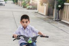 La bicicleta asiática del ejercicio de los estudiantes del niño al aire libre delante del pueblo para el goce biking del entrenam fotos de archivo