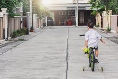 La bicicleta asiática del ejercicio de los estudiantes del niño al aire libre delante del pueblo para el goce biking del entrenam fotos de archivo libres de regalías