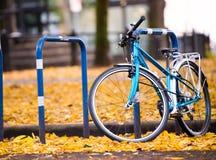 La bicicleta azul se parquea en la calle de la ciudad con el yel caido otoño Fotografía de archivo