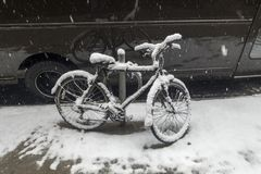 La bicicleta cubierta en nieve parqueó cerca de una furgoneta en la acera del urb fotografía de archivo libre de regalías