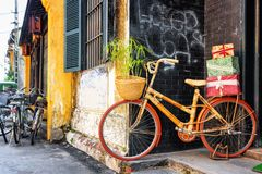 La bicicleta de bambú hecha a mano con las cajas de regalo en el estante parqueó cerca de la pared Fotografía de archivo libre de regalías